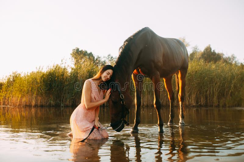 Woman sits next to the horse that drinks water at sunset. A young smiling woman sits next to the horse that drinks water from river at sunset. Backlight royalty free stock images