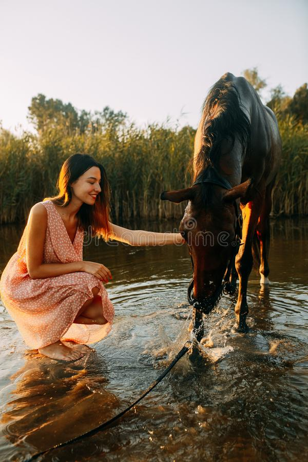 Woman sits next to the horse that drinks water at sunset. A young smiling woman sits next to the horse that drinks water from river at sunset. Backlight royalty free stock photos