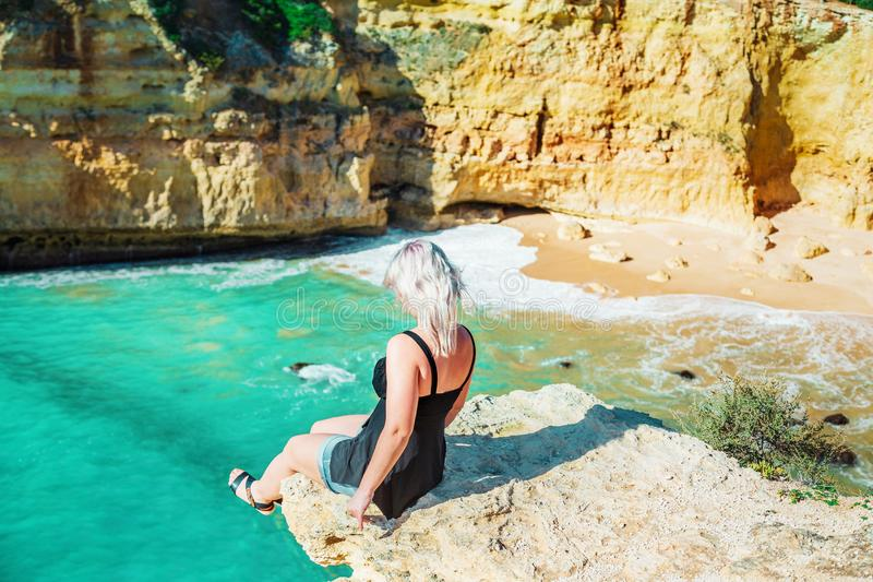 Woman sits on the rock above the blue ocean stock photos