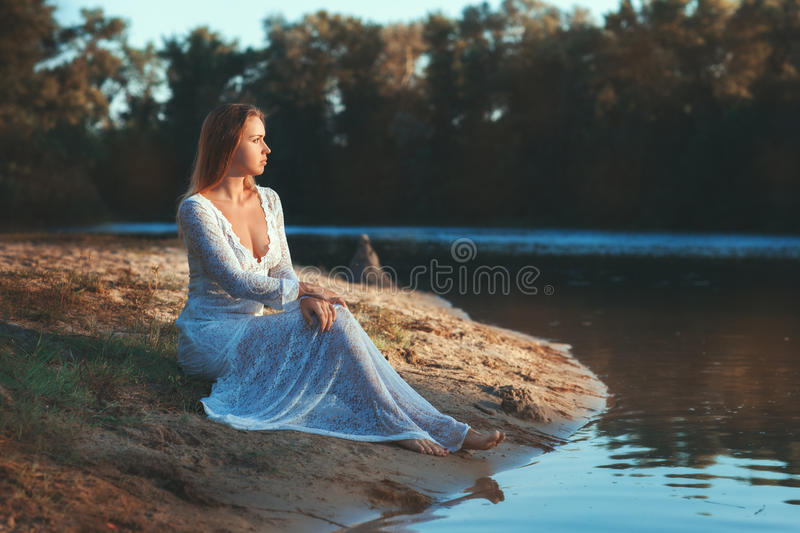 Woman sits on the shore of the lake. royalty free stock photo