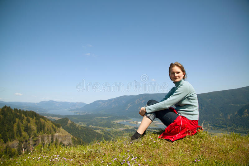 Woman sits at the top of a cliff royalty free stock photography