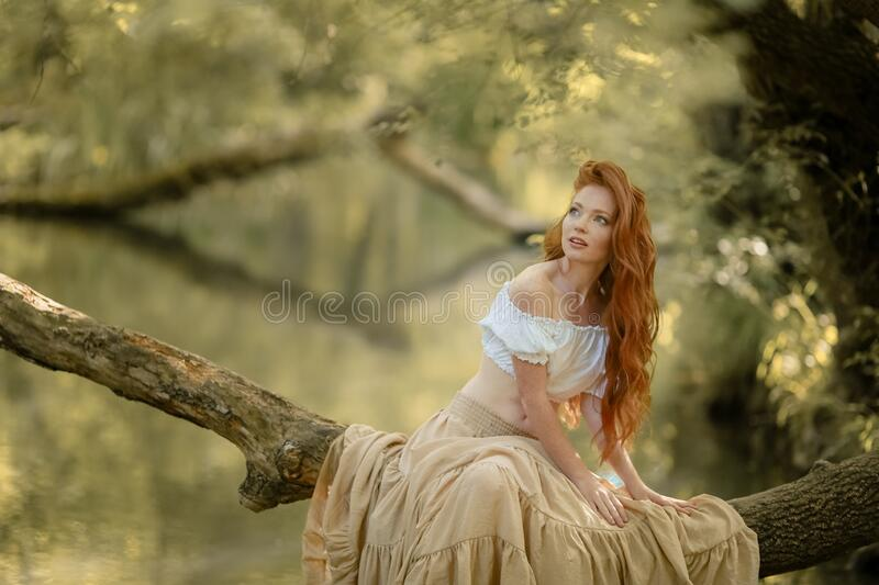 A woman sits on a tree branch lowered over the river.  stock images