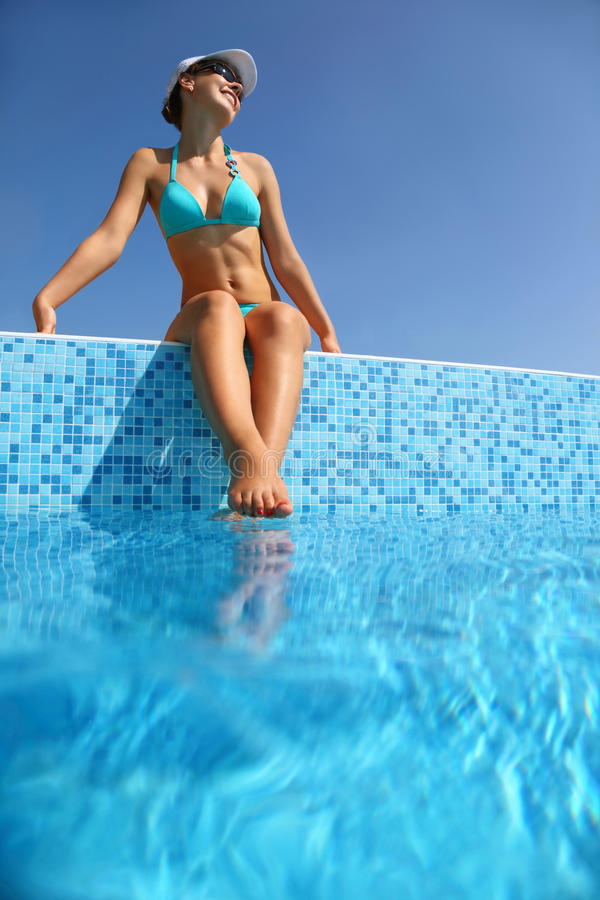 Woman in sits on verge of pool stock photos