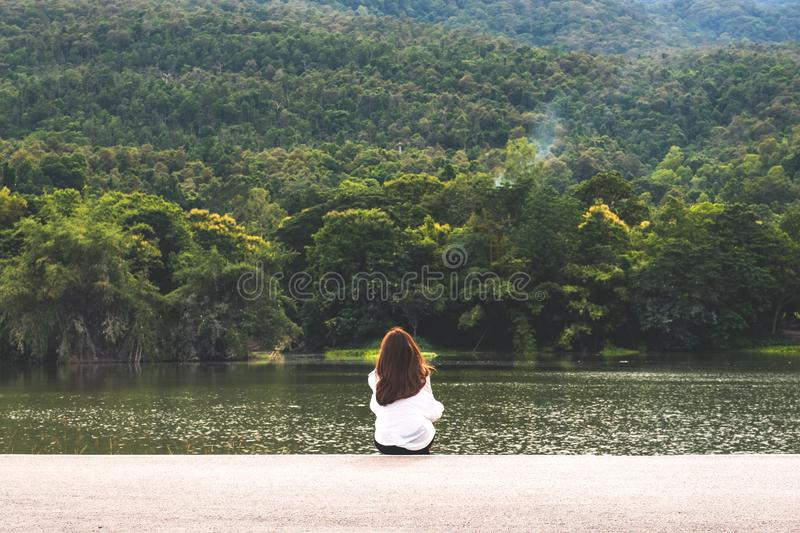 A woman sitting alone by the lake looking at the mountains with cloudy and green nature stock photos