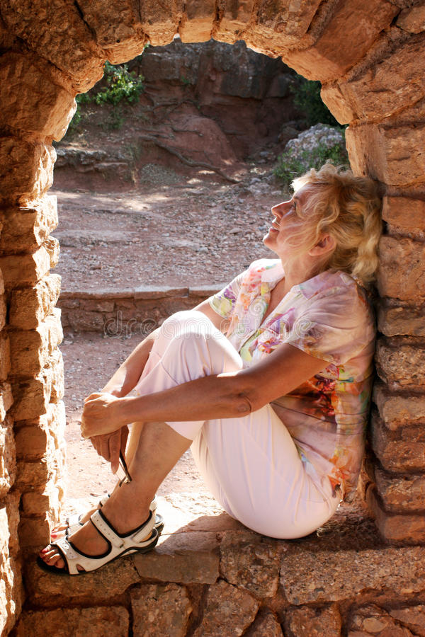 Woman sitting in an arch of old ruins stock images