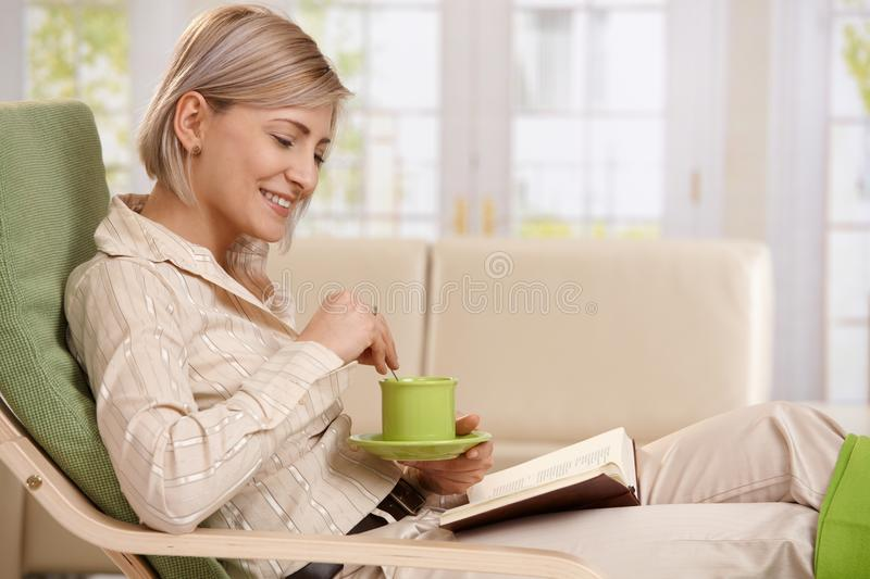 Woman reading with coffee. Woman sitting in armchair, reading book, holding coffee mug, smiling stock photos