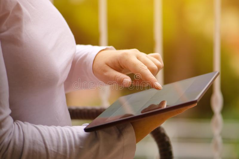 Woman sitting on balcony and using digital tablet computer royalty free stock photography