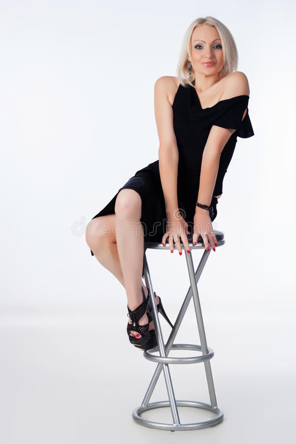 Woman sitting on bar chair. Woman sitting on chair against white background stock photography
