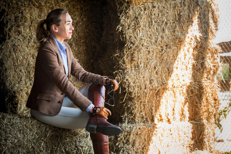 Woman sitting in a barn with hay stock images