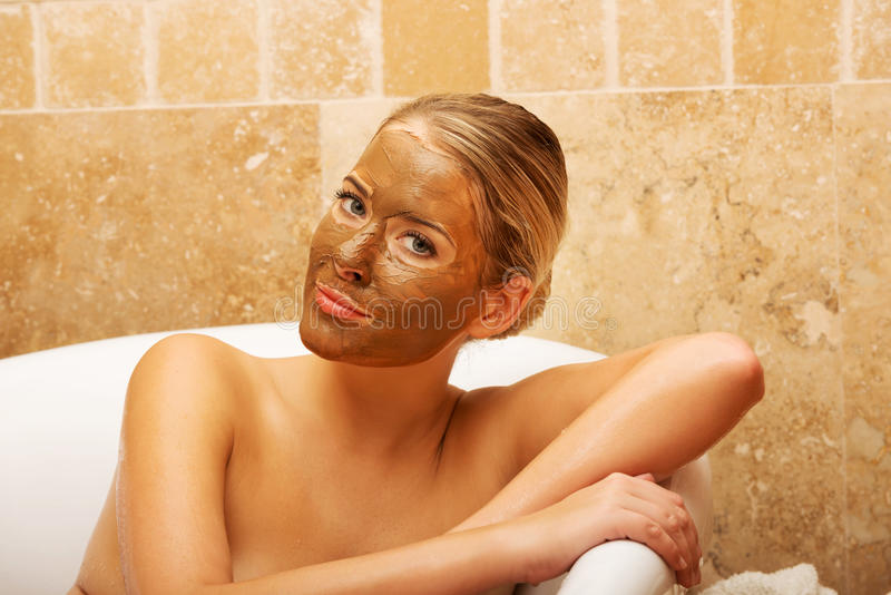 Woman sitting in a bath with face mask royalty free stock photo