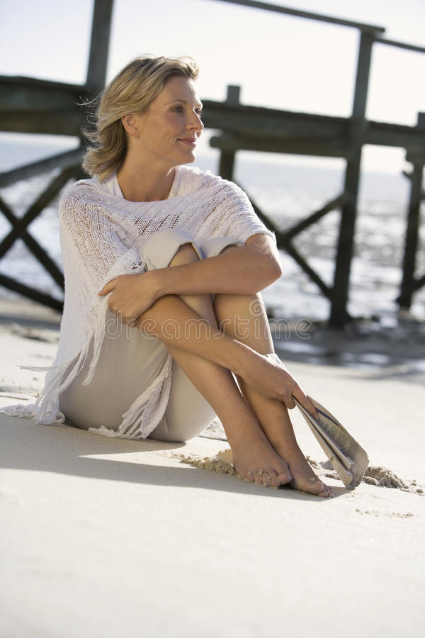A woman sitting on a beach stock image