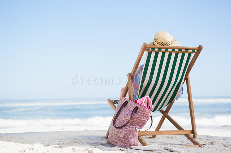 Woman sitting on beach in deck chair. On a sunny day royalty free stock photos