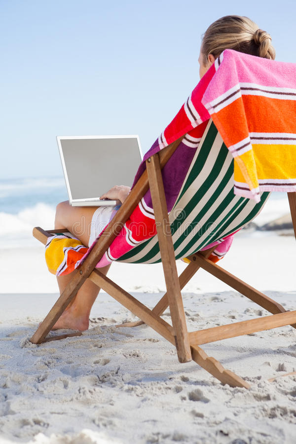 Woman sitting on beach in deck chair using laptop. On a sunny day royalty free stock photography