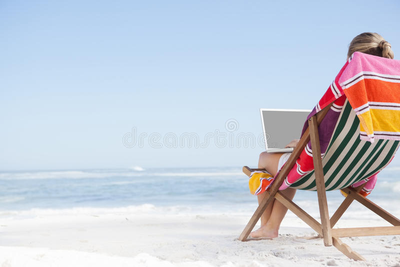 Woman sitting on beach in deck chair using laptop. On a sunny day stock photography