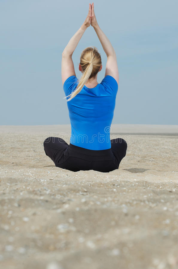 Download Woman Sitting At Beach With Hands Up In Yoga Position Stock Photo - Image: 32625974