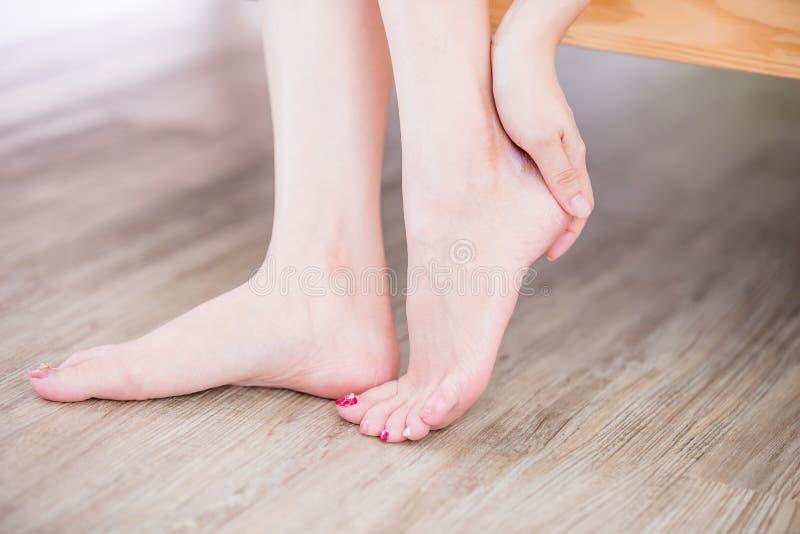 Woman applying cream onto foot stock image