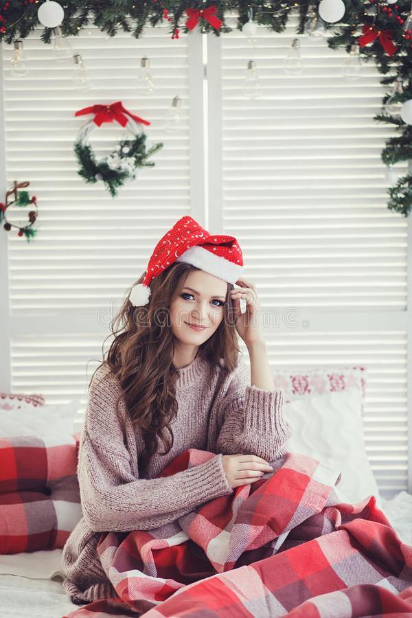 Woman is sitting on the bed at Christmas royalty free stock photography