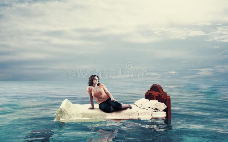 Floating in the ocean. Woman sitting on a bed floating in the ocean stock image
