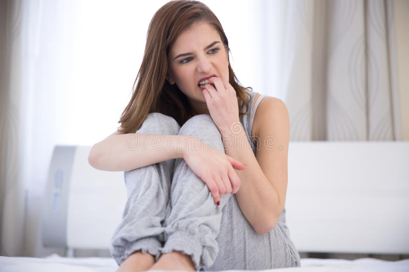 Woman sitting on the bed at home stock photography