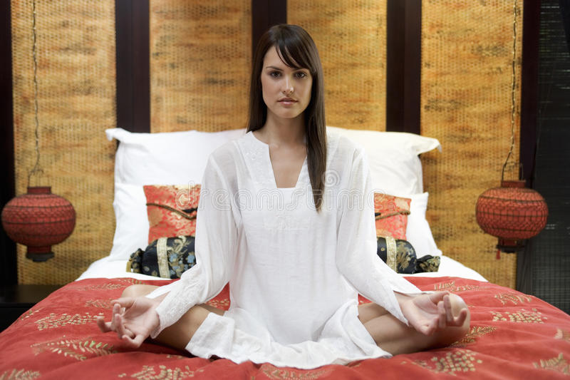 A woman sitting on a bed meditating stock images