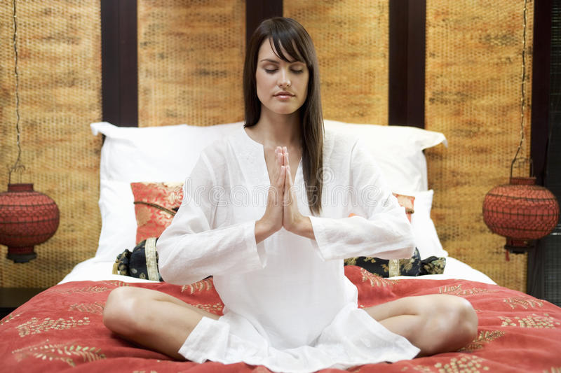 A woman sitting on a bed meditating royalty free stock image