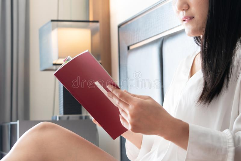 Woman sitting on bed reading the book stock photography