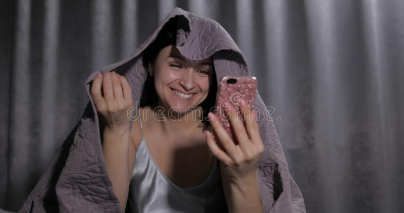 Woman sitting on bed under blanket. Enjoying video chat to friend on smartphone royalty free stock photos