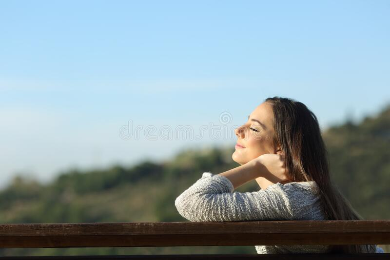 Woman sitting on a bench breathing fresh air in the mountain stock images