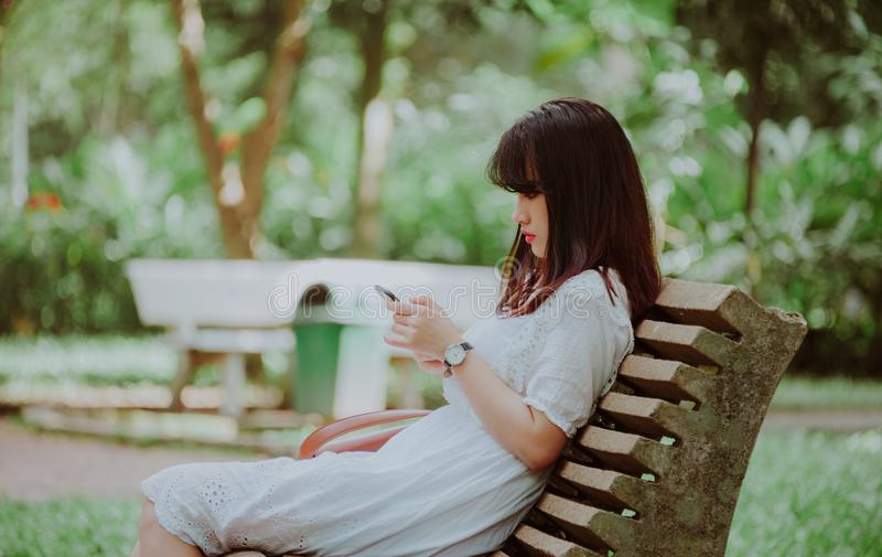 Woman Sitting on Bench Checking Her Phone royalty free stock images