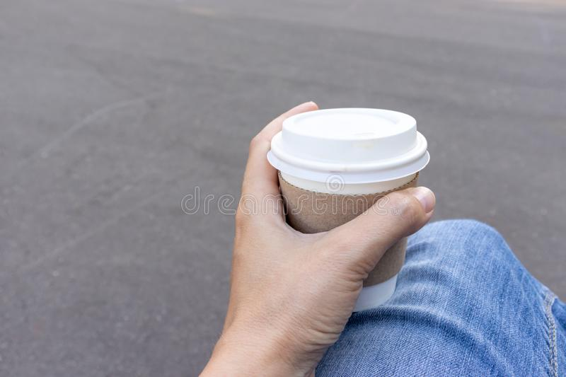 Woman sitting on a bench outdoor and holding a kraft disposadle paper cup of coffee with a white cup in hand royalty free stock photos