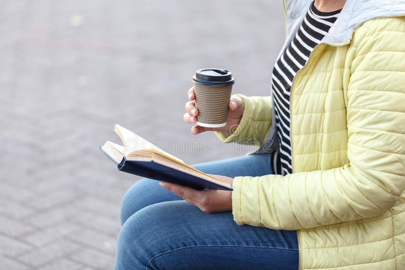Woman sitting on bench and reading book while drinking takeaway royalty free stock image
