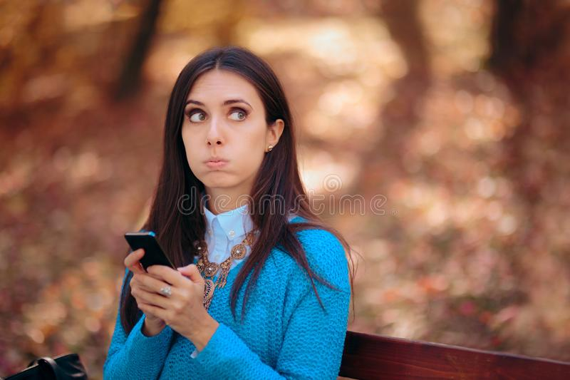Woman Sitting on a Bench Receiving a Strange SMS stock image