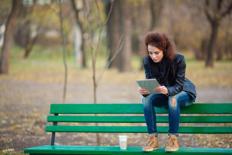 Woman sitting on the bench and using tablet computer royalty free stock photography