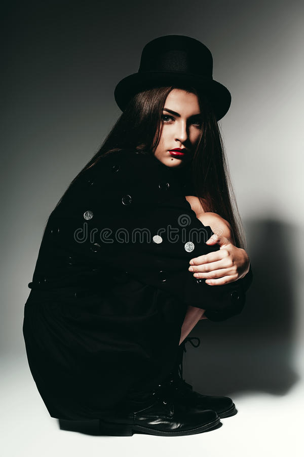 Woman sitting in black dress and hat royalty free stock images