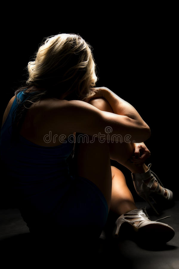 Woman sitting in blue outfit back highlighted royalty free stock image