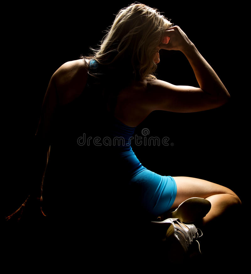 Woman sitting in blue outfit highilighted from back royalty free stock photography