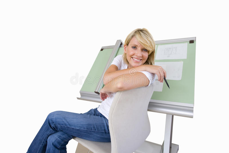 Woman sitting by blue prints on drafting board, smiling portrait, cut out stock image