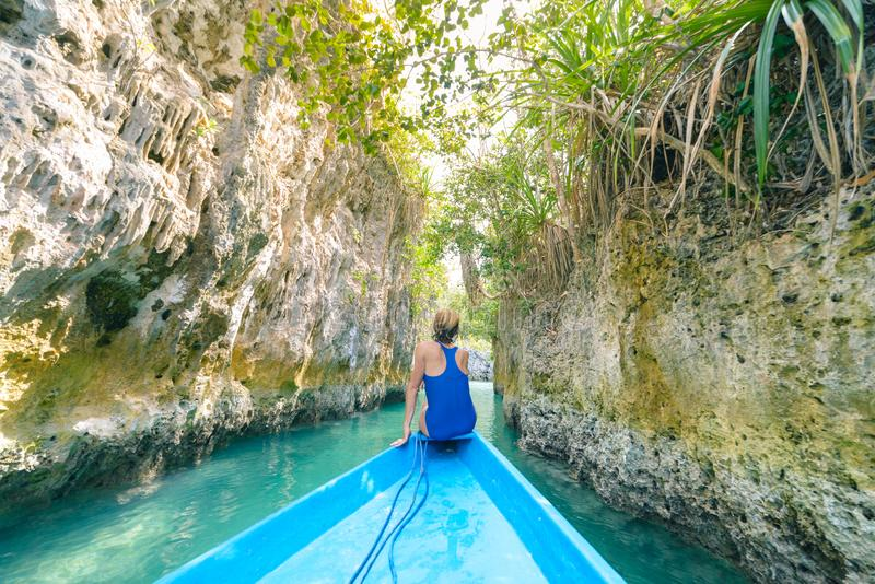 Woman sitting on boat in narrow canyon and turquoise lagoon at Bair Island, tropical paradise pristine coast rainforest blue sea. royalty free stock photo