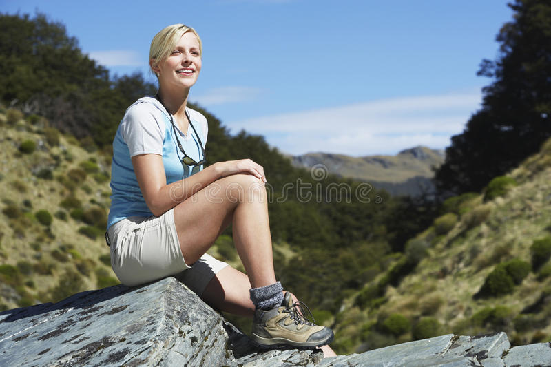 Download Woman Sitting On Boulder In Forest Stock Photo - Image: 31830040