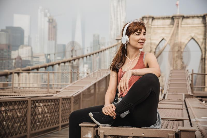 Enjoy the city life. Woman sitting on the Brooklyn bridge and looking the view stock photos