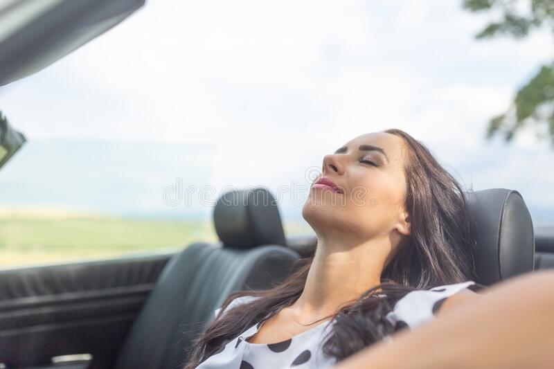Woman sitting in a cabrio car smiling, eye closed, having a rest and nap royalty free stock photo
