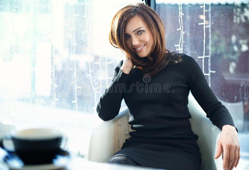 A woman is sitting in a cafe. Close-up, looking at the camera stock photos