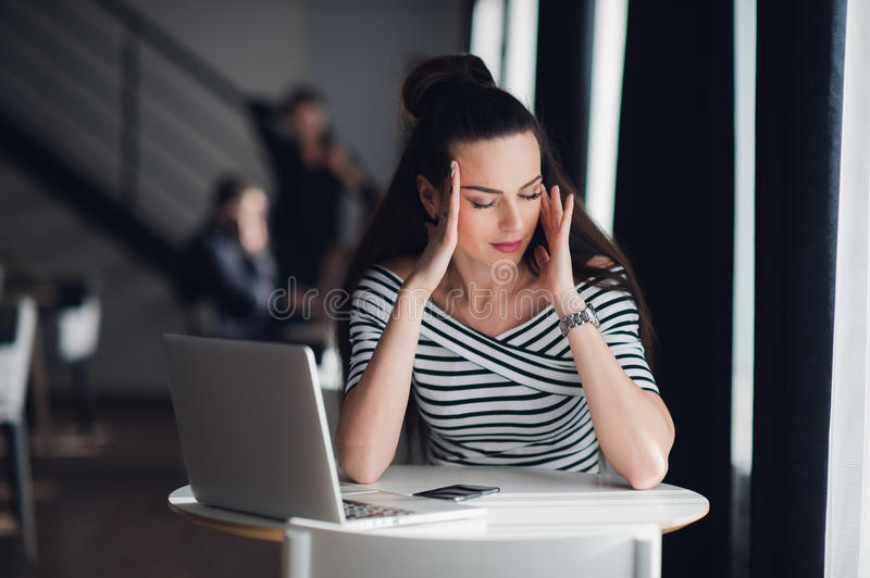 Woman sitting in a cafe in front of a laptop thinking about a problem with her hands touching head. Adult lady trying to royalty free stock photo