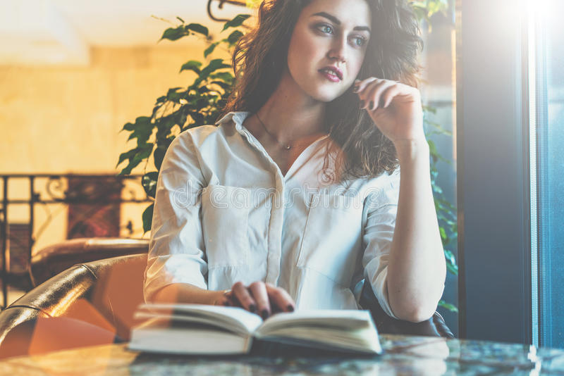 Woman sitting in the cafe at the table with a paper book, address book, journal and looks thoughtfully out the window royalty free stock image