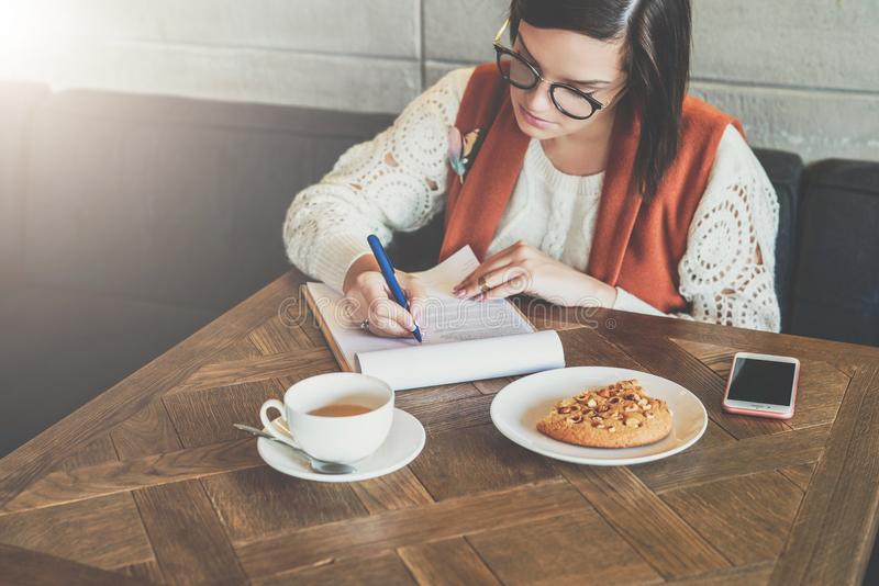 woman is sitting in cafe at table working girl fills out an