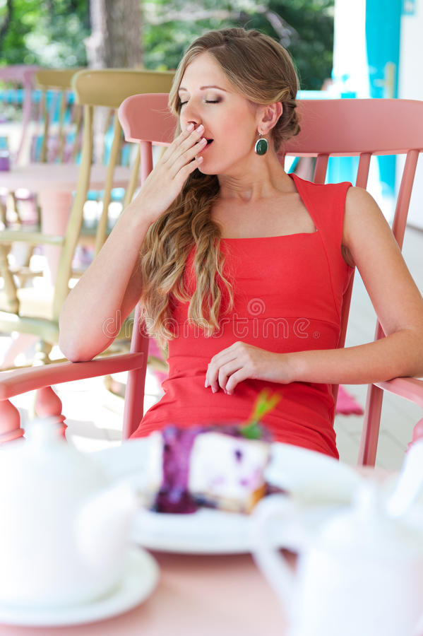 Woman sitting in the cafe and yawning. Sleepy young woman sitting in the cafe and yawning royalty free stock images