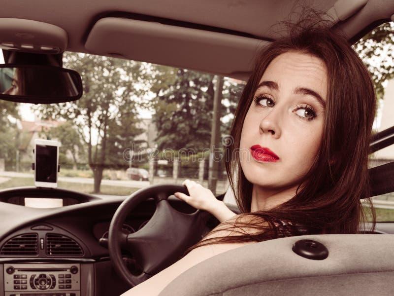 Woman driving car looking backwards stock photography