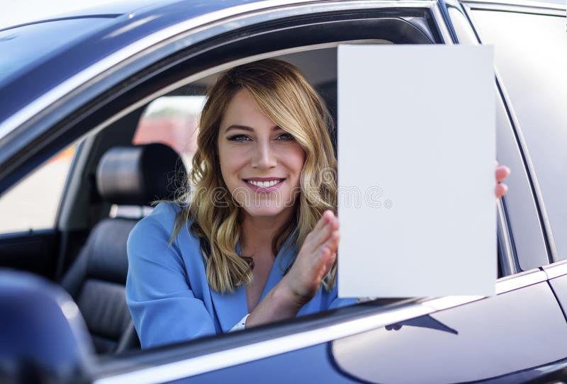 Woman sitting in the car and holding a white blank poster. Attractive blonde with a clean sheet of paper or your text. Focus on model stock photos