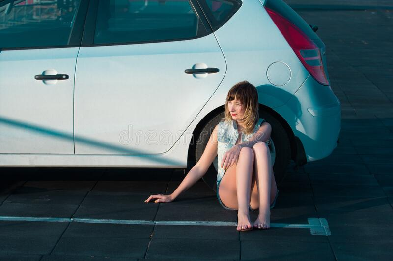 Woman sitting beside car royalty free stock images