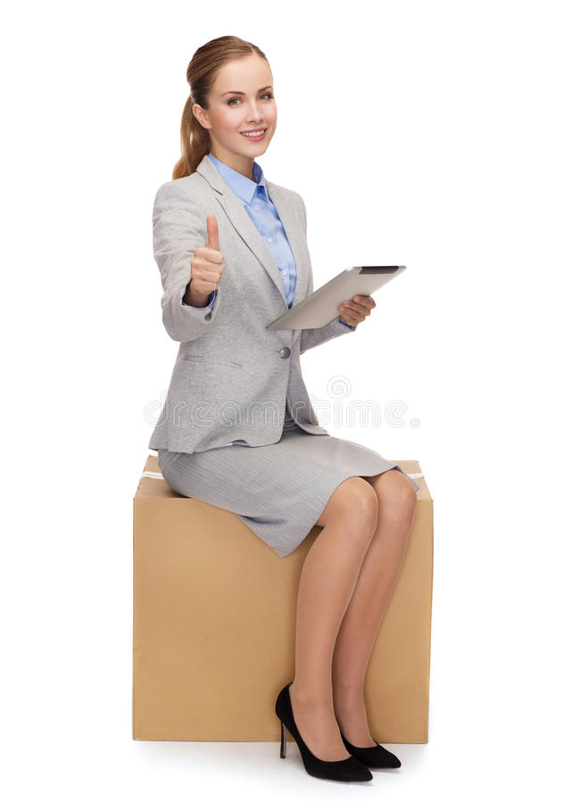 Woman sitting on cardboard box with tablet pc stock image